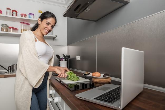 Contenu femme regardant la vidéo sur ordinateur portable et cuisine dans la cuisine