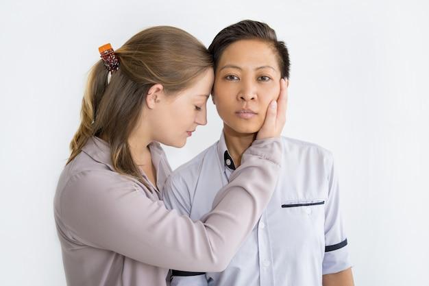 Contenu femme touchant le visage de sa petite amie asiatique