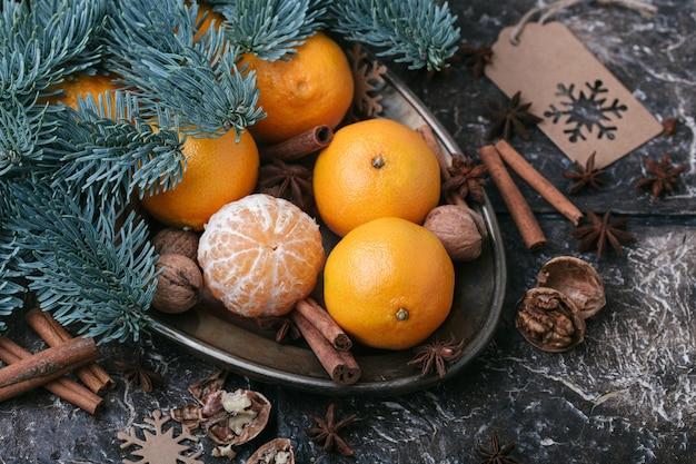 Contenu festif, mandarines, noix, cannelle, cardamome, plat en métal, branche d'épinette, fond marron foncé, vue de dessus