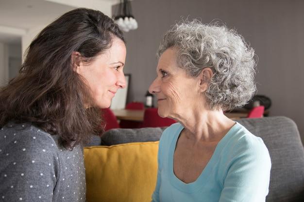 Contenu fille adulte calme et mère senior regardant dans les yeux