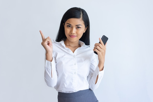 Contenu fille asiatique avec téléphone ayant idée