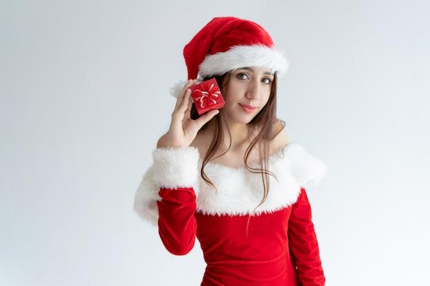 Contenu fille en bonnet de noel montrant un cadeau de noël