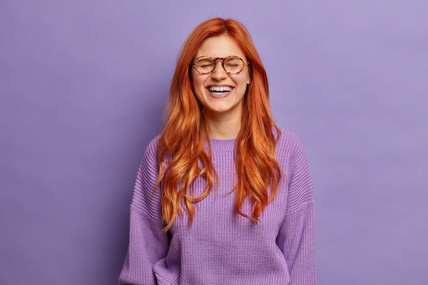 Contenu gaie belle femme au gingembre rit joyeusement a un sourire radieux écoute une blague drôle habillée en pull violet décontracté ferme les yeux porte des lunettes. concept d'émotions et de sentiments positifs