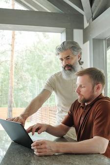 Contenu homme barbu gris moderne assis au comptoir de la cuisine et utilisant un ordinateur portable dans la maison de campagne