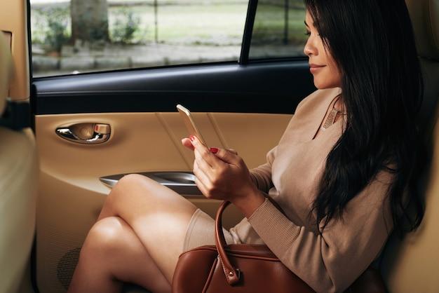 Contenu jeune femme d'affaires asiatique aux cheveux longs assise à l'arrière et utilisant un smartphone pendant les trajets en taxi