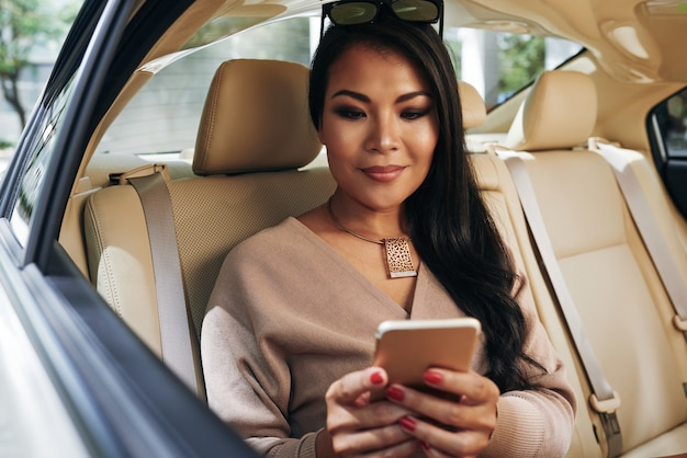 Contenu jeune femme d'affaires asiatique en collier assise sur la banquette arrière d'une voiture haut de gamme et envoyant des sms au téléphone