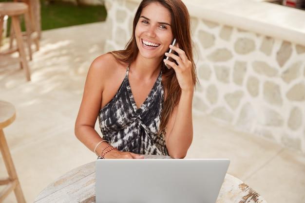 Contenu: jeune journaliste talentueuse et heureuse de parler avec le rédacteur en chef via un téléphone intelligent, de discuter des détails du processus de travail, d'utiliser un ordinateur portable pour rédiger un article, de s'asseoir dans un café confortable
