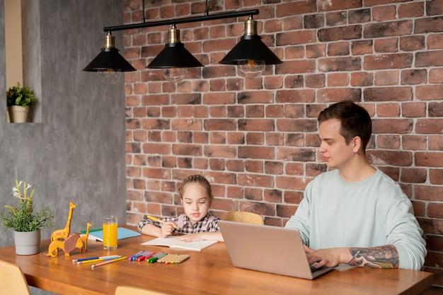 Contenu jeune père hipster avec tatouage sur bras assis à table en bois et travaillant avec un ordinateur portable à la maison pendant que sa fille dessinant une photo avec des crayons