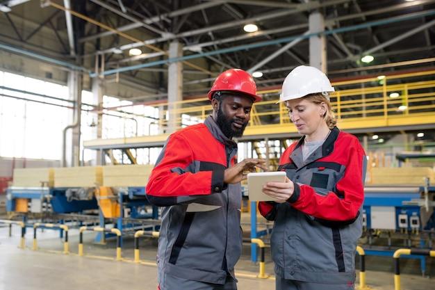Contenu de jeunes collègues multiethniques portant des casques à l'aide d'une tablette tout en discutant des problèmes de fabrication à l'usine de construction