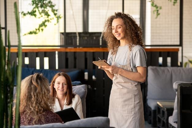 Contenu jolie fille aux cheveux bouclés assis dans un café confortable et utilisant un ordinateur portable tout en interagissant sur les médias sociaux, site de rencontres