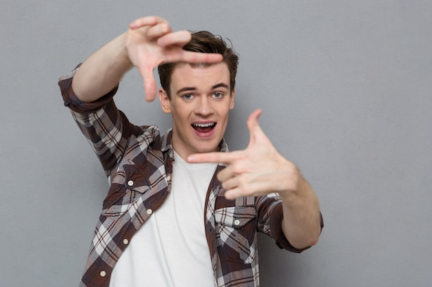 Contenu joyeux joyeux excité beau jeune homme en chemise à carreaux faisant un cadre avec les doigts devant son visage