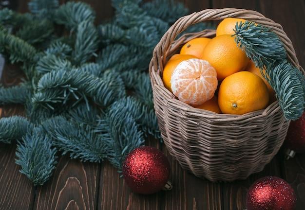 Contenu de vacances, mandarines, mandarine pelée dans un panier en osier, vintage, branche d'épinette, boules rouges d'arbre de noël, fond brun foncé, vue de dessus