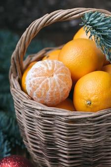 Contenu de vacances, mandarines, mandarine pelée dans un panier en osier, vintage, branche d'épinette, gros plan, fond marron foncé