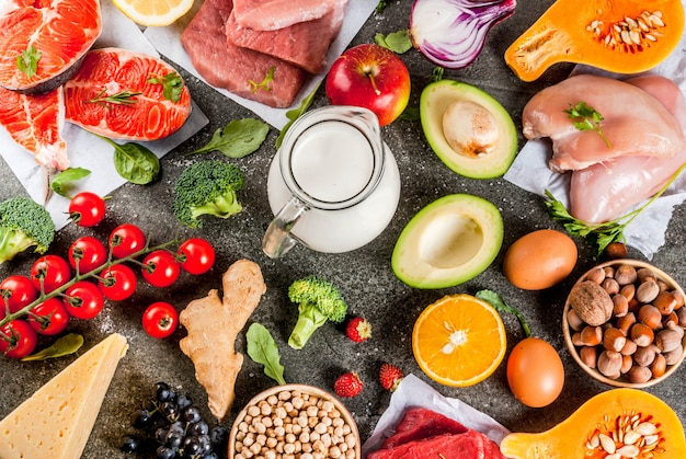 Contexte d'une alimentation saine. ingrédients alimentaires biologiques, superaliments: viande de bœuf et de porc, filet de poulet, saumon, haricots, noix, lait, œufs, fruits, légumes. table en pierre noire, vue de dessus du fond
