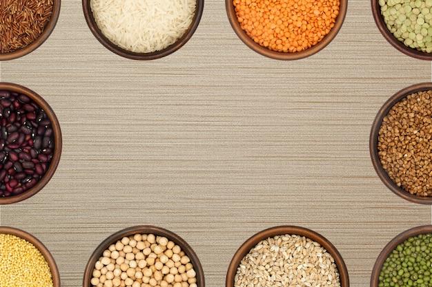 Contexte - des bols avec diverses céréales et légumineuses forment un cadre