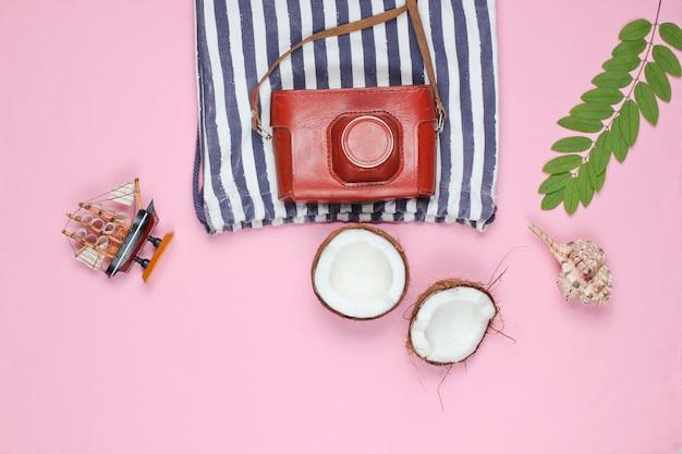 Contexte créatif de l'été. sac de plage rayé, accessoires sur fond rose. vue de dessus.