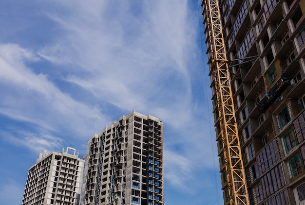Contexte du chantier de construction. grues et nouveaux bâtiments à plusieurs étages contre le ciel