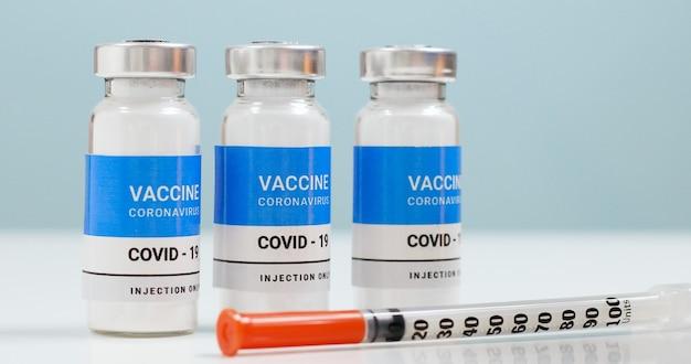 Contexte du coronavirus sars-cov-2 avec flacon de vaccin et seringue pour injection en laboratoire. recherche et développement d'un nouveau remède contre les maladies
