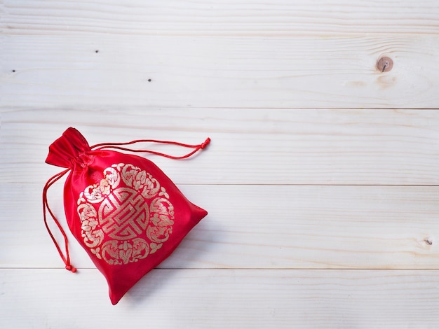 Contexte du nouvel an chinois. sac d'argent soyeux rouge avec ficelle sur fond de bois de pin naturel et espace de copie.