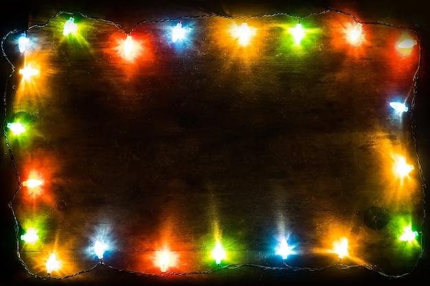 Contexte du nouvel an. fond de noël guirlande de noël avec des lumières colorées et des lampes sur un fond en bois. espace libre pour le texte