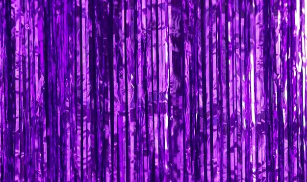 Contexte du parti. décor en papier violet, guirlandes et bonbons.