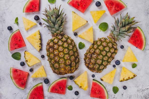Contexte d'été avec des portions d'ananas et de pastèque