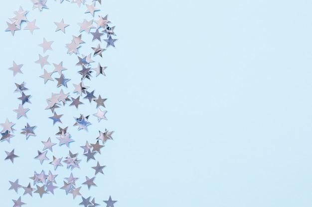 Contexte festif abstrait de noël avec des étoiles de confettis de feuille d'argent sur bleu