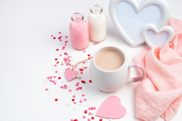 Contexte pour le 14 février avec une tasse de café avec du lait, un cadre en forme de cœur et une bouteille de lait