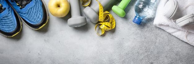 Contexte de remise en forme avec des haltères, des baskets, une serviette, des écouteurs et une bouteille d'eau