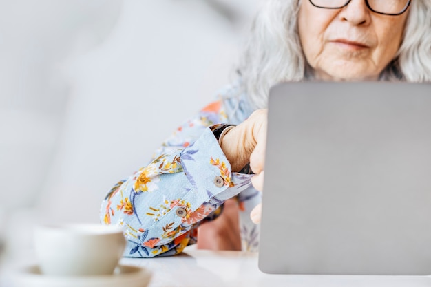 Contexte de réseautage de médias sociaux avec une femme âgée travaillant sur un ordinateur portable