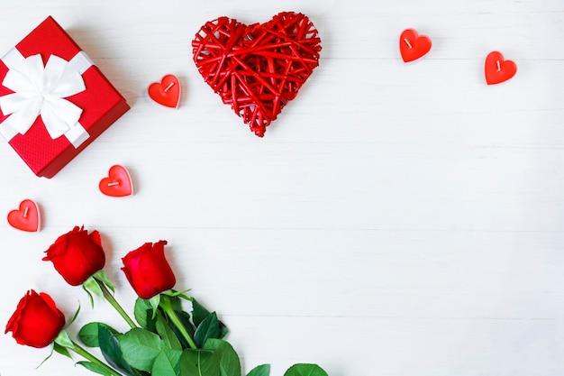 Contexte de la saint-valentin. cadeau, roses et bougies rouges sur fond blanc