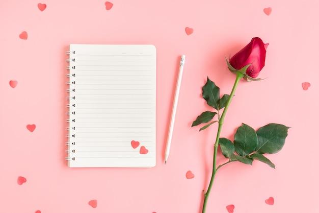 Contexte de la saint-valentin. cahier, petits coeurs et rose sur rose pastel