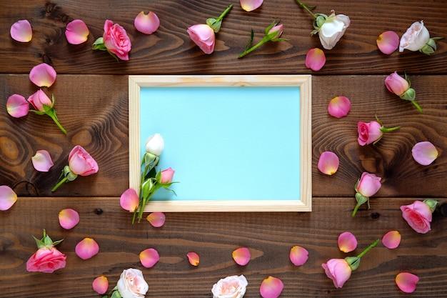 Contexte de la saint-valentin. motif floral de cadre rond composé de roses roses et beiges, feuilles vertes sur fond en bois. mise à plat, vue de dessus.