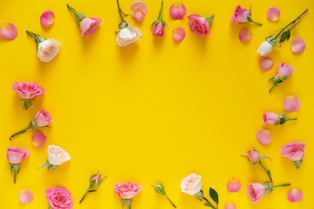 Contexte de la saint-valentin. motif floral cadre rond composé de roses roses et beiges, feuilles vertes sur fond jaune. mise à plat, vue de dessus.