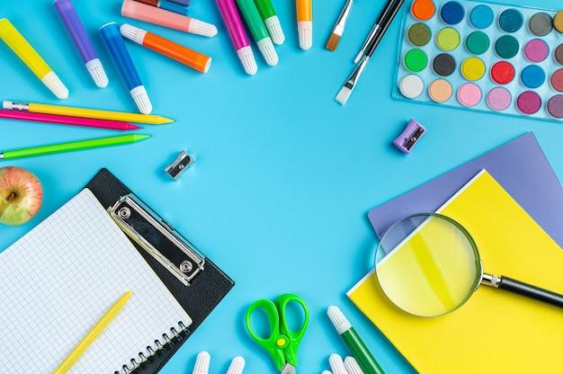 Contexte scolaire un cadre de diverses fournitures de bureau sur fond bleu