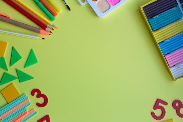 Contexte scolaire avec fournitures scolaires sur jaune, stylo, crayons, marqueurs, aquarelles, pâte à modeler, taille-crayon, nombres, formes géométriques, bâtons de comptage, mise à plat, espace de copie