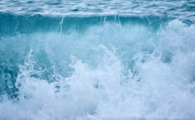 Contexte - surf de mer par temps nuageux, gros plan de vague déferlante