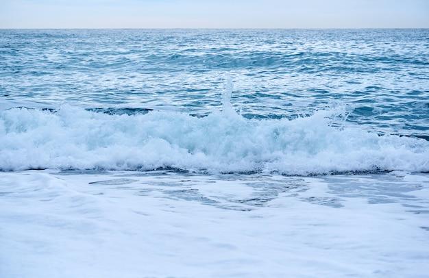 Contexte - surf de mer par temps nuageux, vague déferlante