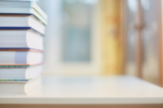 Contexte sur le thème de la formation, de l'éducation. bureau avec livres, bibliothèque et fenêtre en flou. concept d'école ou carte de voeux avec le début de l'apprentissage.