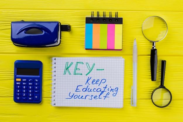 Continuez à vous renseigner sur le concept à plat. bloc-notes avec stylo et accessoires de bureau de papeterie sur bois jaune.