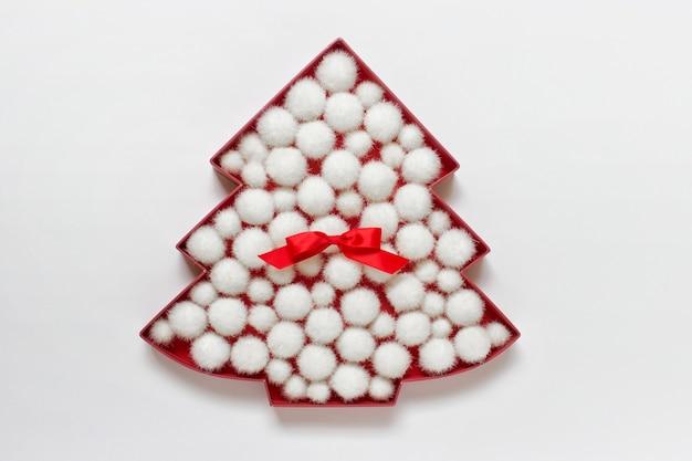 Contour d'arbre de noël rouge rempli de boules moelleuses blanches et noeud de satin rouge sur une surface blanche.
