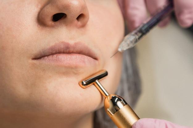 Contour en plastique. cosmétologue injecte une toxine botulique pour resserrer et lisser les rides sur la peau d'un visage féminin.
