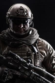 Contour rétro-éclairage portrait de soldat des forces spéciales en uniforme avec des armes, portrait sur fond noir