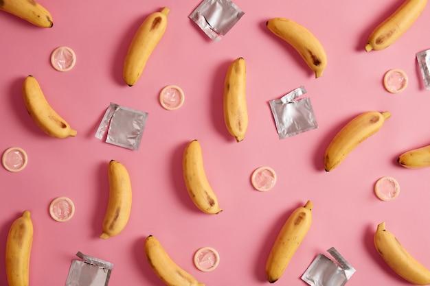 Contraception, concept érotique. bananes jaunes et préservatifs non emballés autour. sensibilisation au sida. composition à plat. des relations sûres. fond rose. protège toi. prévention des maladies vénériennes