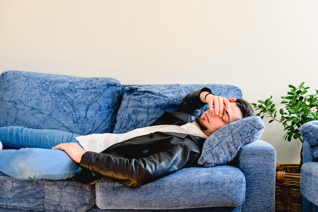 Contrarié jeune homme allongé sur un canapé au repos à la maison se sentir fatigué, fatigué, souffrant de migraine