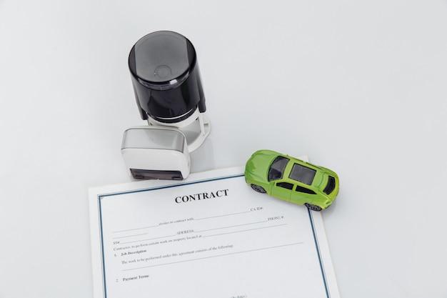 Contrat d'achat d'une voiture avec timbres et voiture jouet.