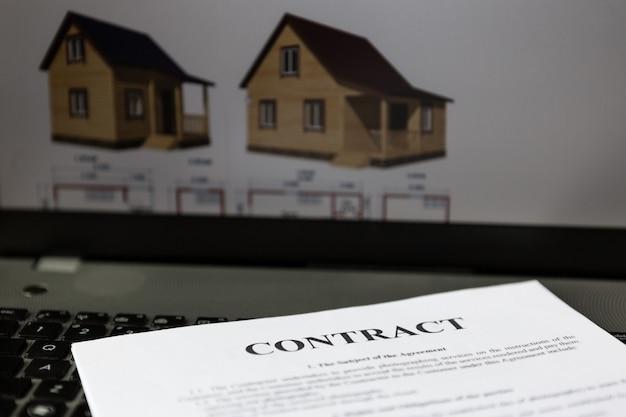 Le contrat est sur l'ordinateur portable. a l'écran, un dessin de la future maison.