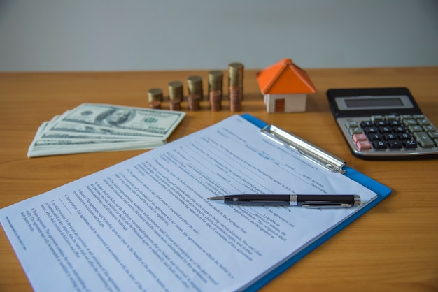 Contrat hypothécaire pour la vente de biens immobiliers avec un stylo et des clés de la maison