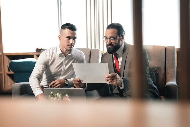 Contrat avec l'investisseur. jeune homme d'affaires prometteur signant un contrat important avec un investisseur barbu