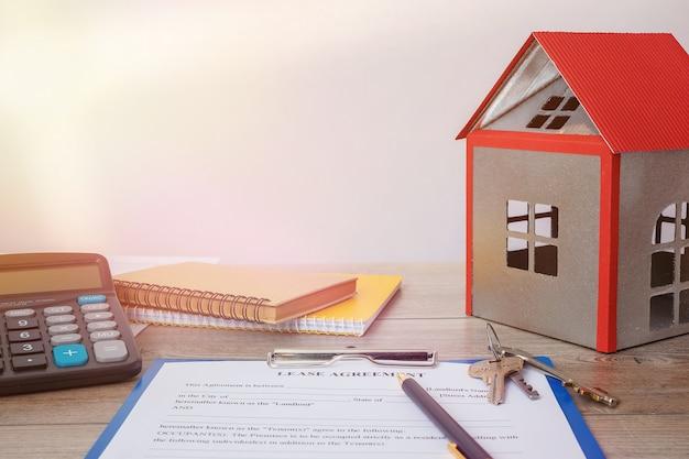 Contrat de location immobilier vierge, modèles de maison, clés et calculatrice sur bureau
